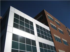 Tuality Healthcare's office building is a five story red brick structure with silver colored metal and glass accents.