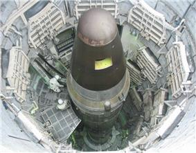 View looking down a textured metal cylindrical enclosure. Inside sits a long, thin missile that is cylindrical in shape with a conical nose.