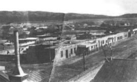 A grainy, black and white photograph showing several single story buildings next to a dirt road. Several homes and other buildings stretch toward the mountains in the distance. A chimney is seen in the foreground.