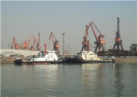 two black and white tugboats berthed against a background of large cranes