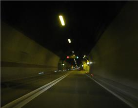 Inside of Mala Kapela Tunnel when operated as a single tube tunnel featuring a double solid line dividing the traffic lanes and variable traffic signs indicating two way traffic in the tunnel.