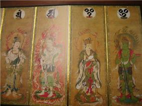 Four deities on four sections of a folding screen. Two of them are female and dressed in robes. The other two are male and only sparely dressed. All four have halos with flames.