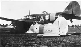 Rear three-quarter view of two military monoplanes lying wheels down on a field, one atop the other