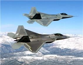 Two F-22s overflying snow-capped mountains.