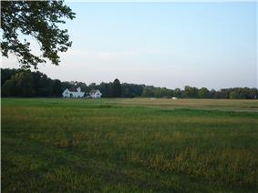 View across a field to a large white building and woods