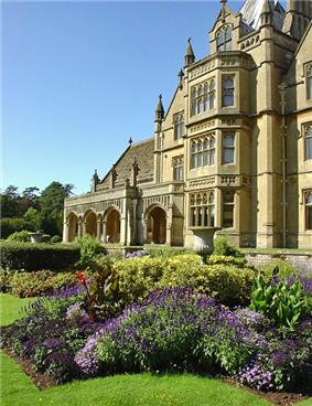 Yellow stone ornate facade of building with lower arched front to the left. In the foreground could flowers in formal garden.