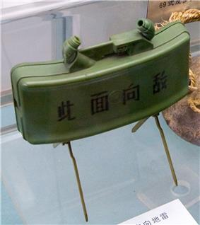 A green plastic-bodied mine supported by a pair of scissor legs, with the text
