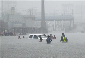 People wading through waist- to chest-deep water towards a pickup truck