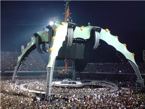The tour stage. The video screen was above the band in a large black container. Four silver legs supporting the screen curved down into the audience. Five circular orange lights were dotted along the top of each leg. The round stage was surrounded by a semi-circular catwalk which can be reached by crossing a bridge. The audience surrounded the band on all sides.