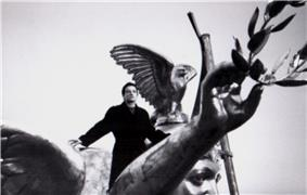 Bono standing atop a large statue of an angel.