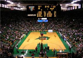 Interior of a basketball arena with the scoreboard and stands visible.