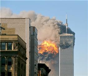 Two tall, gray, rectangular buildings spewing black smoke and flames, particularly from the left of the two.