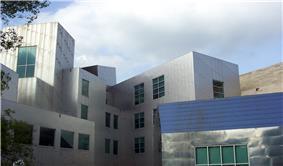 An exterior shot of a silver, uneven building