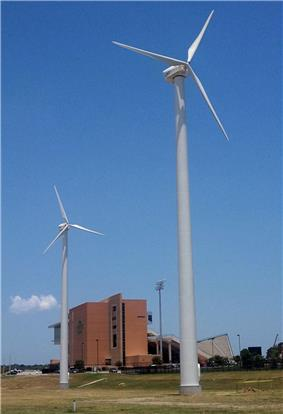 A photograph of two wind turbines in front of an empty college football stadium