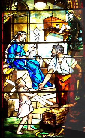 The Holy Family are outside their carpenter's shop where Joseph is working at his bench and Mary is sitting on the steps, spinning with a distaff. Joseph looks towards Mary as the child Jesus carries some wood resembling a cross.