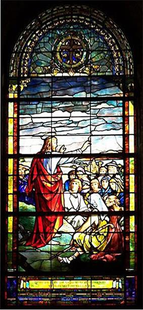 Christ standing on mountain, stretches his arm towards the  people gathered to hear Him speak.