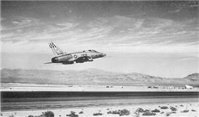 Rear quarter view of a single engine jet fighter taking off from a runway located in a desert. The bare metal finish jet has a checkerboard unit insignia on its vertical tail. The landing gear are raised. The horizon is hilly.