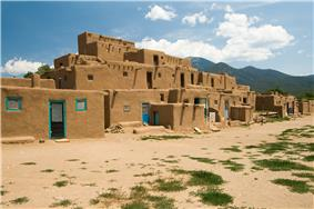 A cluster of reddish brown small adobe houses with blue doors and window frames.