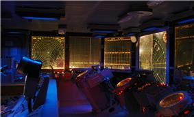 Interior photograph of the combat information center aboard the USS Hornet. Illuminated display boards cover the walls, and several duty stations with large dials stand in the dim room.