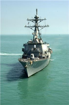 A grey warship in murky water