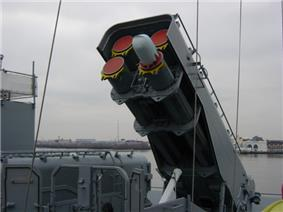 A large gray box mounted on a platform, tipped at a roughly 45-degree angle facing the camera. A missile is sticking out from the front of the canister.