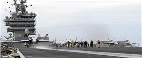 Three gray F/A-18 Hornet strike fighter aircraft line up across the frame for catapult launches from an aircraft carrier's deck. Support staff is seen on the deck throughout, while exhaust can be seen from the engines of the right-hand aircraft.