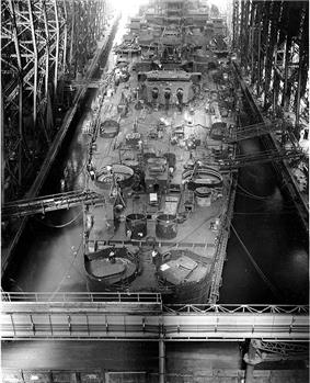 A large ship is being built. Seen from the stern, one of the 12-inch turrets equipped with three guns is visible. Most of the deck is cluttered with part of the ship in various stages of completion. Walkways connect the ship to the sides of the building ways.