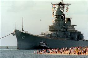 A large gray ship moves toward the camera and slightly to the left. On the right, a number of people on a beach are observing the ship as she moves in to pass them with the aid of a tugboat.
