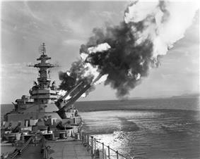 A black-and-white photograph of a large caliber gunship on the left side of the picture with the main guns pointed to the top right side of the image. Smoke and flames can be seen from the barrels of the guns as they have just been discharged. A disturbance on the water generated from the pressure of the gun's firing can be seen on the bottom right of the image.