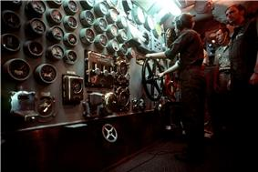 A large panel with many dials. A man works a wheel at the far right end of the image.