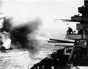 Seen from the side of a ship as large guns fire toward targets out of sight