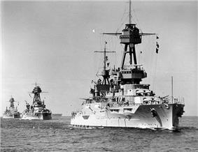 Three large warships steaming in single file through the water
