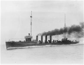 A black-and-white photo of the warship. Shown in motion with black smoke billowing from its four smokestacks, the ship has two masts but no sails.