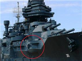 A permanently docked museum ship with a red circle on the photograph to highlight a gun protruding from an opening in the ship's port side.