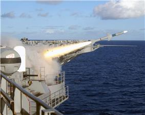 Firing of a missile from USS Roosevelt while at sea, seen from the flight deck. There is a Phalanx cannon on the left, with a white, domed upper section and a black cannon on the lower part.