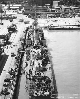 Historic photograph of the USS Wadleigh at dock and under work at the Mare Island Naval Shipyard in 1945. Shipyard buildings are visible in the background.