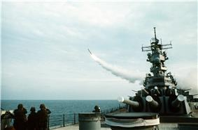 A forward view of a ship with large gun barrels pointing forward. To the left, a missile is flying away from the ship.