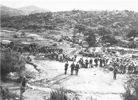 A large group of soldiers, some standing and some sitting, in a clearing below a hill covered in low grass and a few trees which can be seen in the background. In the middle ground a line of military vehicles are parked in a line on a road running front-on towards the camera, before hooking to the left in profile. Soldiers work around the vehicles, unloading stores.