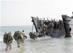 Colour photograph of marines wading into an amphibious landing craft.