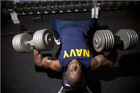 A navy man performs strength training exercises.