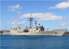 A grey warship sailing near the shoreline.