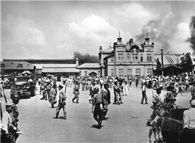 A city square filled with soldiers and civilians. Smoke is in the sky in the background behind a large building