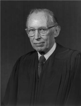 monochrome photographic portrait of a white man in late middle age in judicial robes.  He wears glasses and has thinning hair.