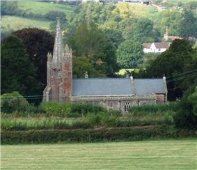 Gray stone building with square tower surmounted by a spire on the left. Surrounded by trees and green fields.