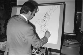 A man drawing a cartoon character on a large vertical drawing board