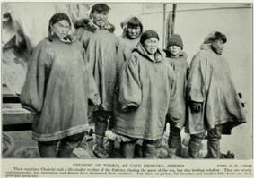 Six people, maybe parents and four children, all wearing long voluminous smock-like outer garments and large boots. Some wear close-fitting hats. Five are staring suspiciously at the camera, one is looking away.