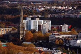 A view looking down towards a tall church spire which rises high above the surrounding trees and large modern buildings, with rows of hillside housing in the distance