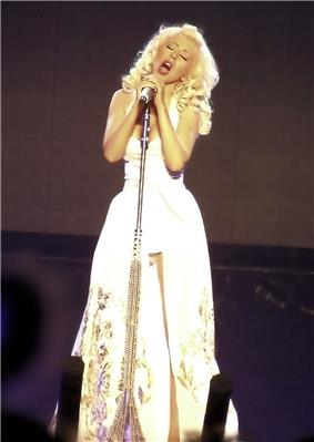 A blond woman dressed in white singing to a microphone.