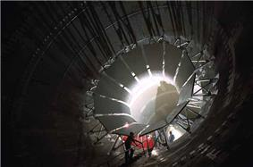 Photograph of workers working on large vanes arranged around the inside perimeter of the Unitary Plan Wind Tunnel.