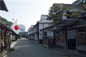 Street lined with wooden houses with white walls.